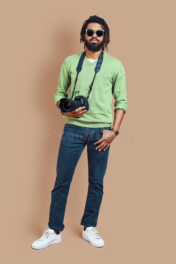 Full length of young African photographer stock image