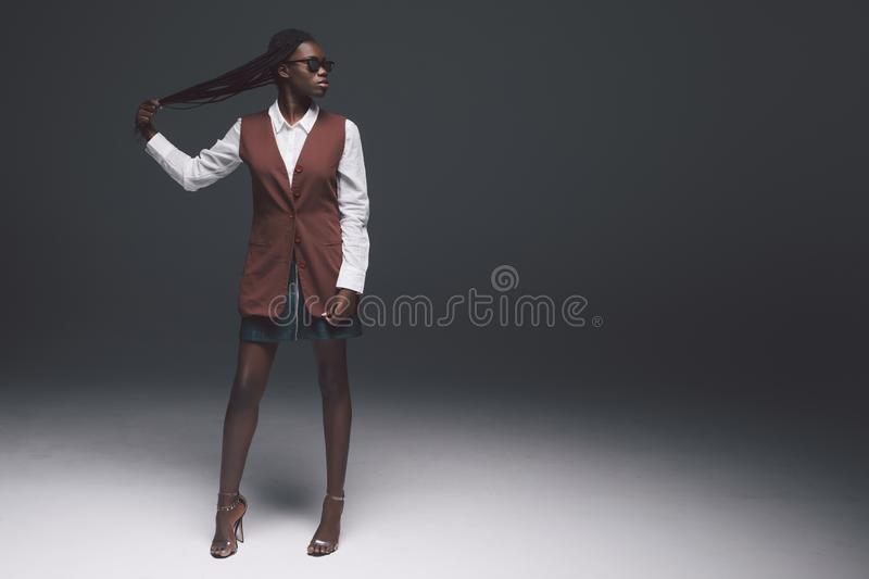 Full Length of a young african woman in fashion clothes with sunglasses against black wall background stock photography