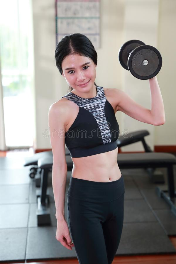 Young asian healthy woman who love health is exercising by lifting dumbbell in fitness with smiling face workout in gym concept stock photography