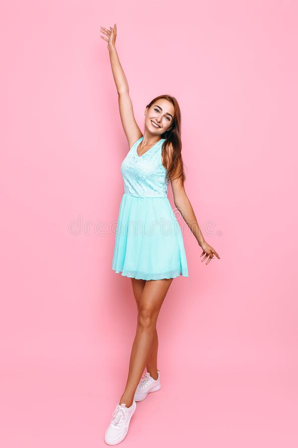 Full length, young beautiful girl in dress having fun on pink background stock images