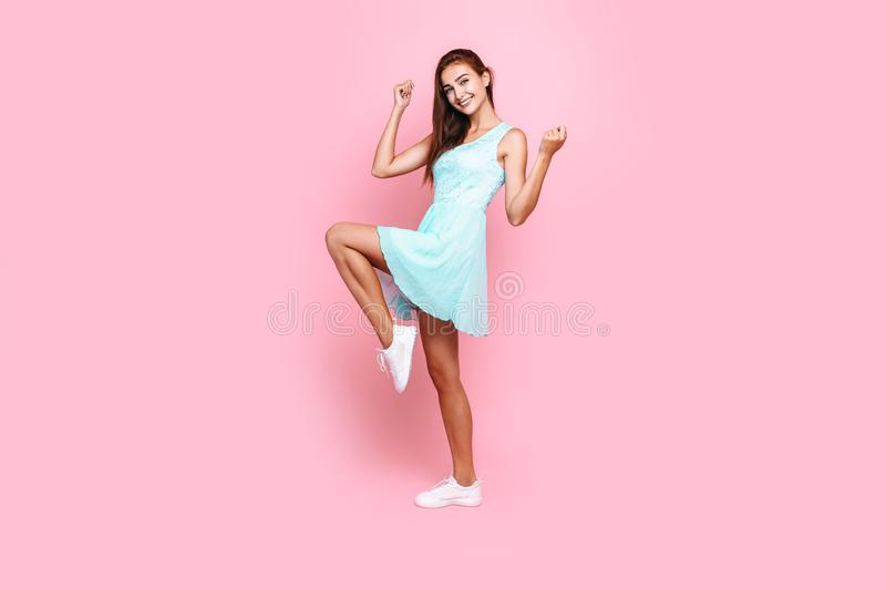 Full length, young beautiful girl in dress having fun on pink background stock photos
