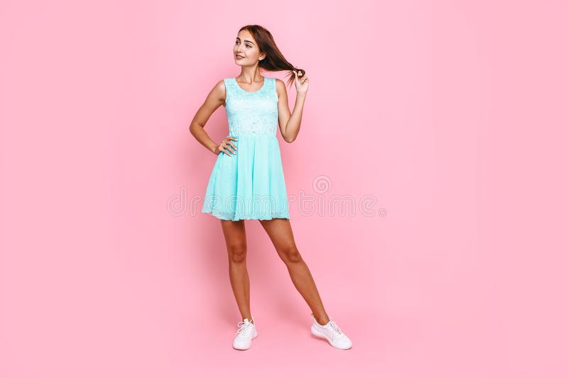 Full length, young beautiful pensive girl in dress, on pink background stock image