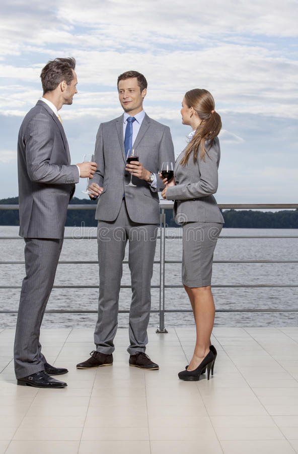 Full length of young businesspeople holding wineglasses while communicating on terrace royalty free stock image