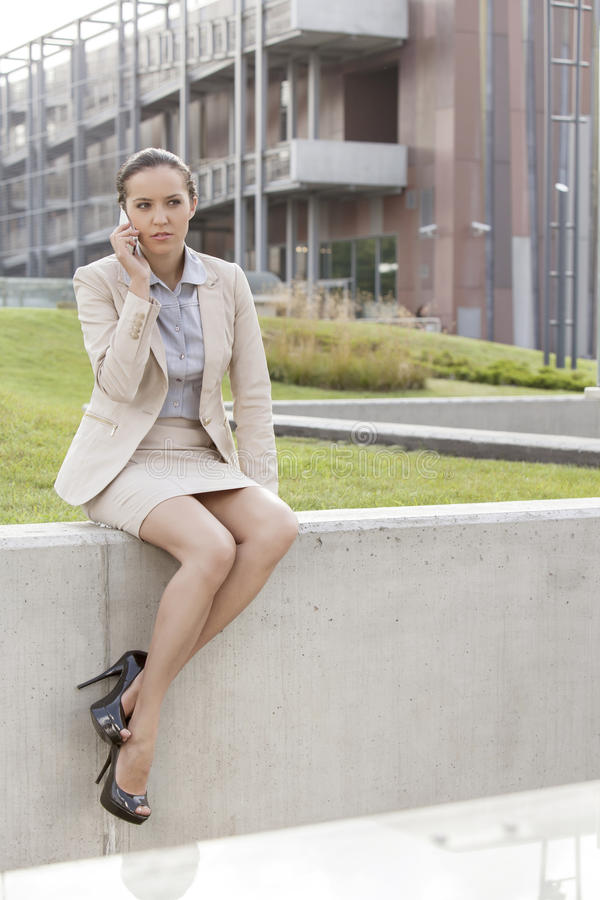Full length of young businesswoman using mobile phone while sitting on wall against office building royalty free stock images