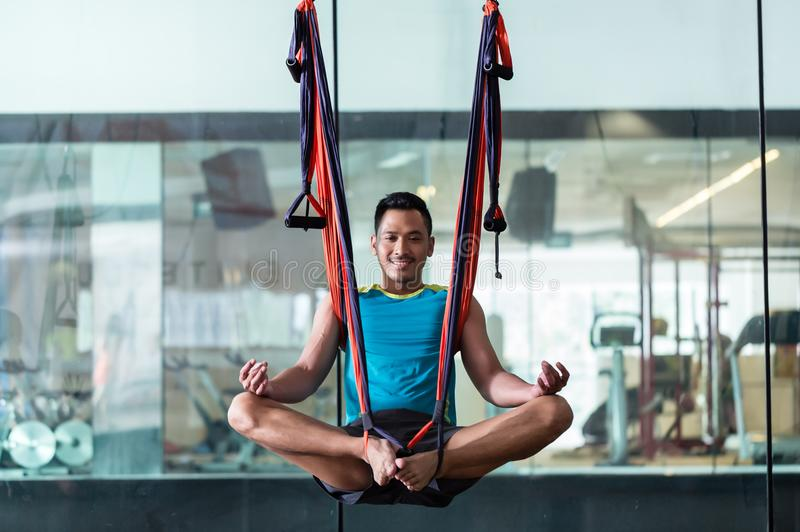 Full length of a young confident man hanging in lotus position w royalty free stock photography