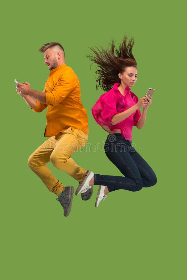 Full length of young couple with mobile phone while jumping stock photo
