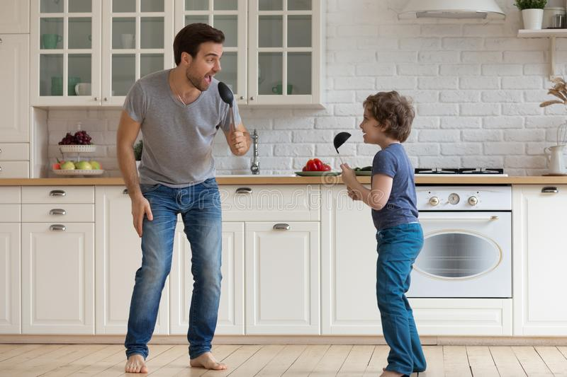 Full length young father with happy son holding soup ladles. Full length overjoyed young father with happy little school age boy son holding soup ladles as stock photography
