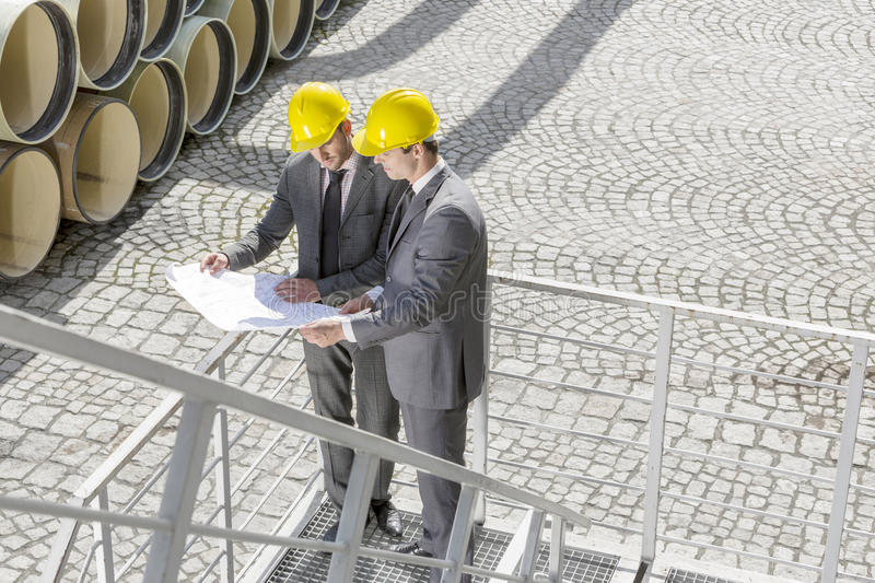 Full length of young male engineers examining blueprint on stairway royalty free stock photos