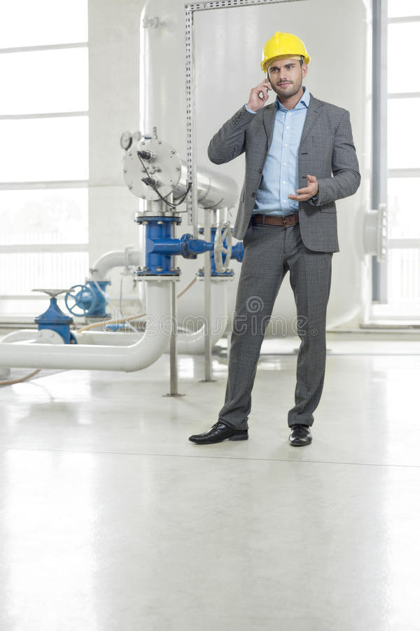 Full length of young male manager using cell phone in industry stock image