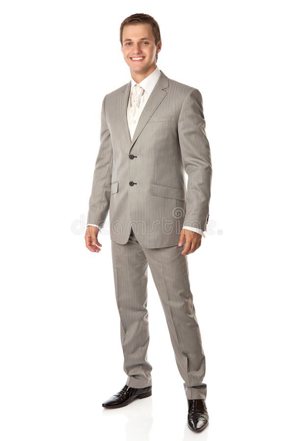 Full length of a young man in a suit smiling brigh royalty free stock photography