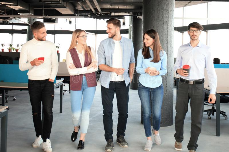 Full length of young people in smart casual wear discussing business and smiling while walking through the office. royalty free stock photos