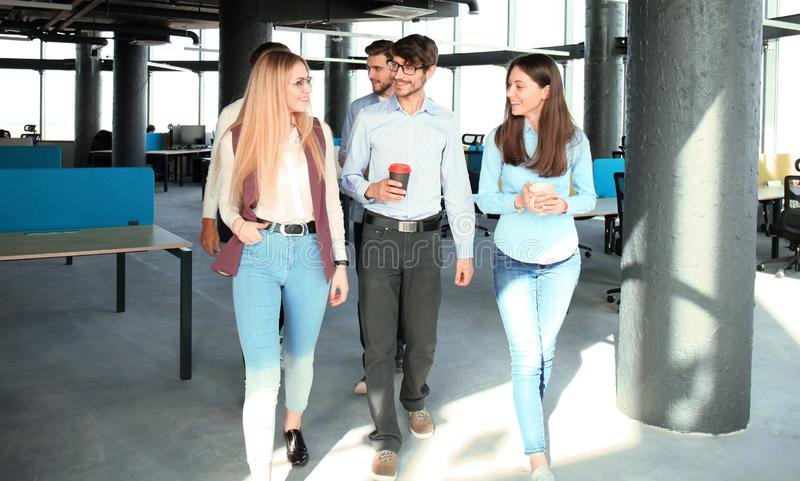 Full length of young people in smart casual wear discussing business and smiling while walking through the office. stock photo