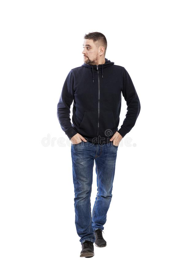 A full-length young unshaven brunette man in a blue hoodie and jeans goes forward and looks away. Isolated over white background. stock photography