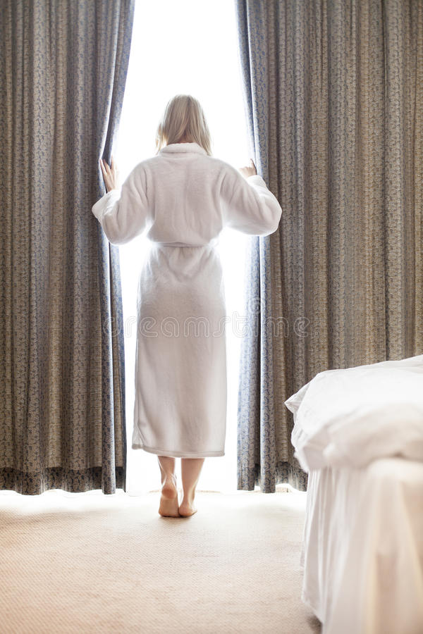 Full Length Of Young Woman In Bathrobe Opening Bedroom