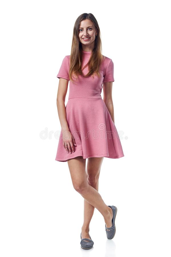 Full length of young woman in pink dress stadnign casually. Full length of young woman in pink dress standing casually over white background royalty free stock image