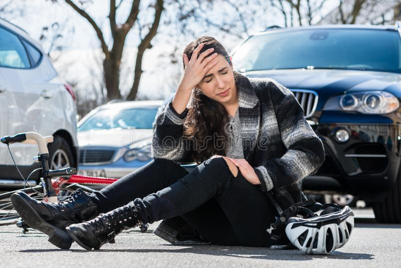 Young woman sitting on the asphalt after bicycle accident stock images