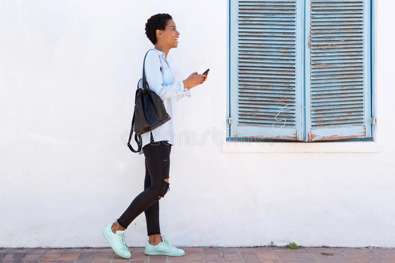 Full length young woman walking with cellphone and bag stock images