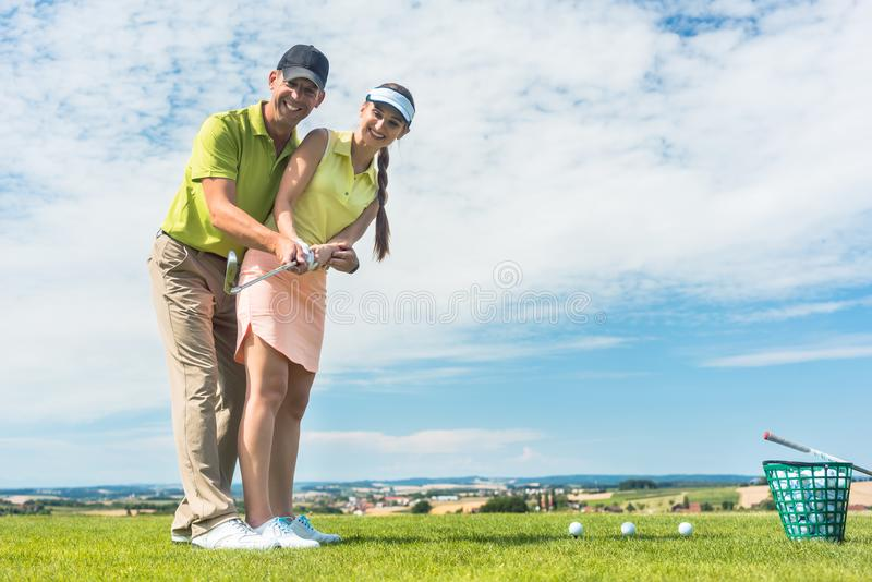 Young woman practicing the correct move during golf class with a skilled player. Full length of a young women smiling while practicing the correct move for royalty free stock photo