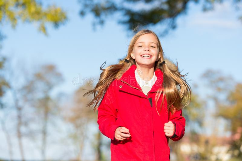 Full of life energy. Child cheerful on fall walk. Warm coat best choice for autumn. Autumn outfit concept. Kid girl wear stock photography