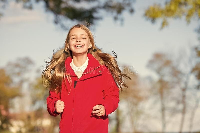 Full of life energy. Child cheerful on fall walk. Warm coat best choice for autumn. Autumn outfit concept. Kid girl wear. Coat for autumn season nature royalty free stock photo