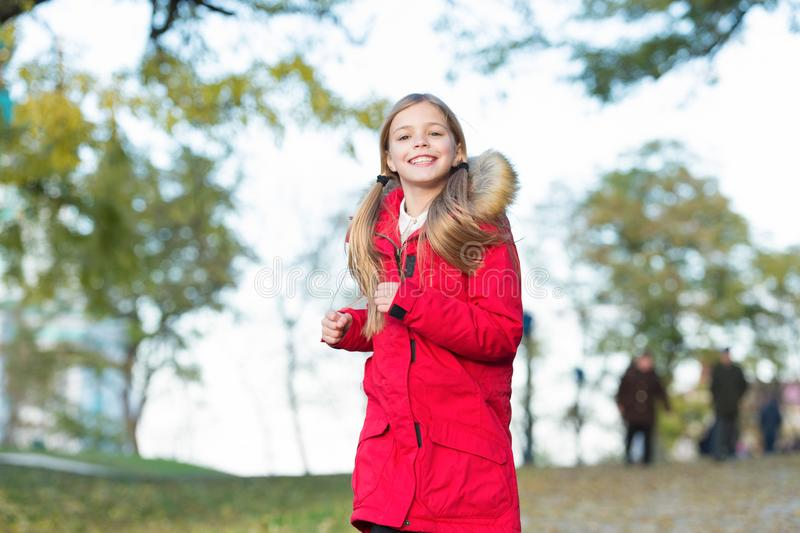Full of life energy. Child cheerful on fall walk. Warm coat best choice for autumn. Keep body warm clothes autumn days stock images