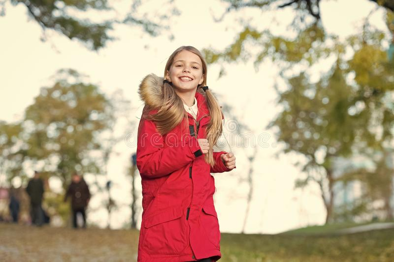 Full of life energy. Child cheerful on fall walk. Warm coat best choice for autumn. Keep body warm clothes autumn days. Autumn outfit concept. Kid girl wear stock image