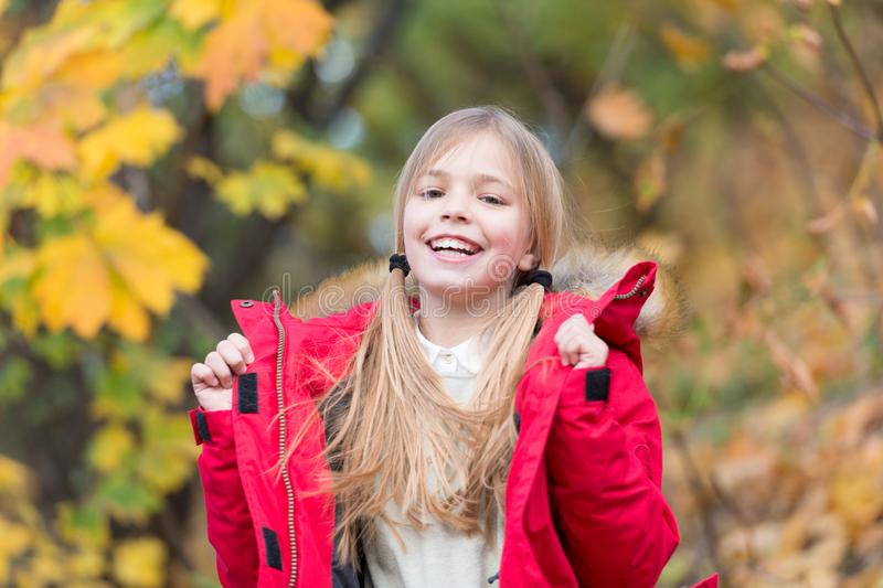 Full of life energy. Kid girl wear coat for autumn season nature background. Child cheerful on fall walk. Warm coat best. Choice for autumn. Keep body warm stock image