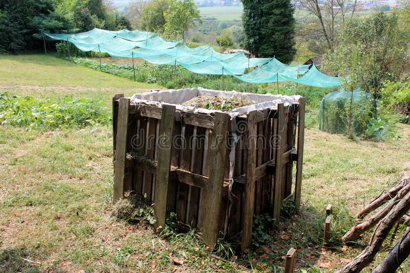 Full makeshift outdoor homemade wooden compost box made of wooden pallets surrounded with grass and plants in local urban garden royalty free stock image
