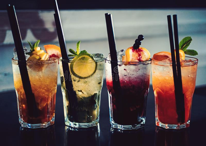 A full measure of bars. Cocktail drinks served in glasses with straws. Iced drinks in cocktail glasses. Alcoholic mixed. Drinks with ice. Juicy beverages with royalty free stock image