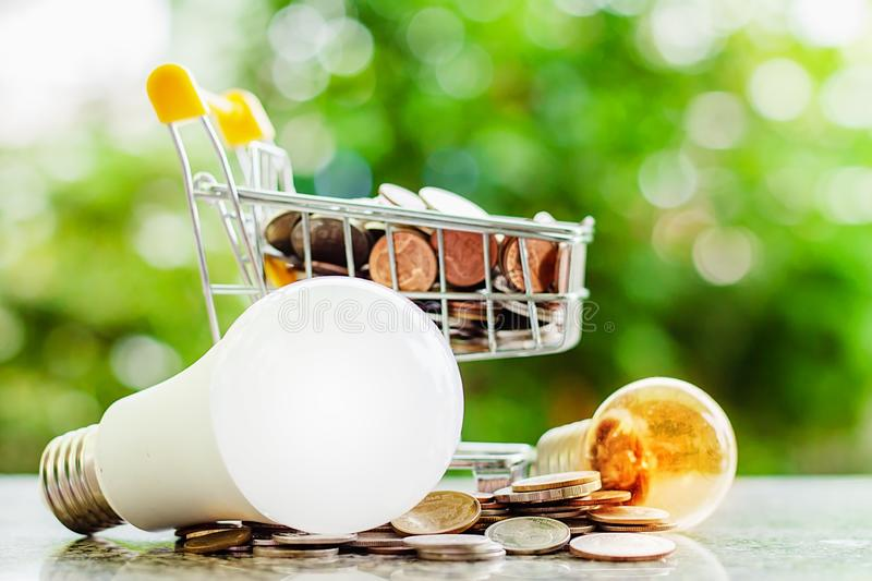 Full of money coin in mini shopping cart or trolley with led lam stock photography