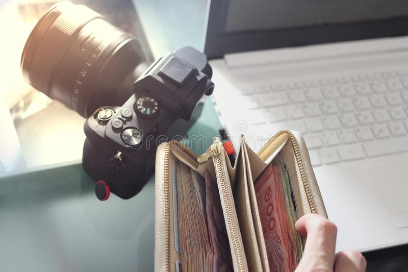 Full of money wallet hand and notebook computer on blur camera background with sun light royalty free stock images