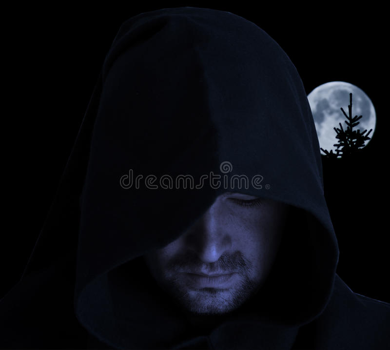 Full moon. Man in an ancient hood on a full moon background