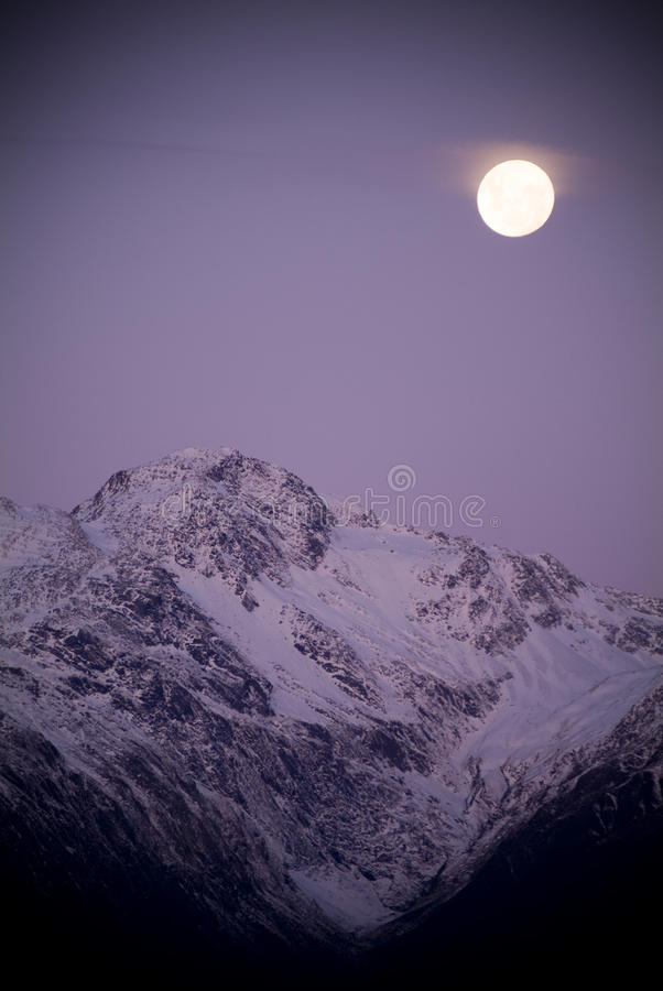 Full Moon. Moon rising over snow capped mountain bathed in purple dusk light royalty free stock images