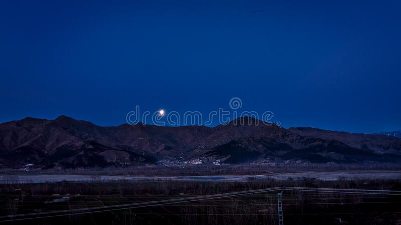 Full Moon Above the Mountain Ranges Near Town stock image