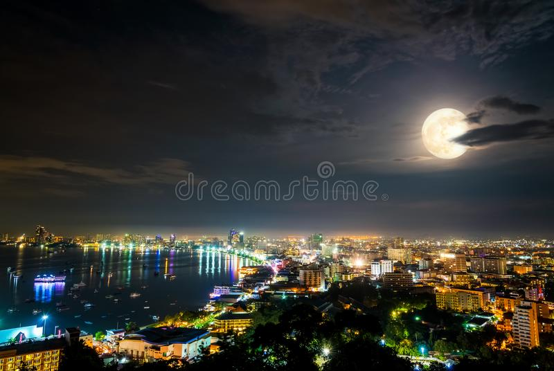 Full moon above Pattaya City at night, Thailand. High view on viewpoint full moon above cityscape with colorful light at the sea beach of Pattaya stock photo