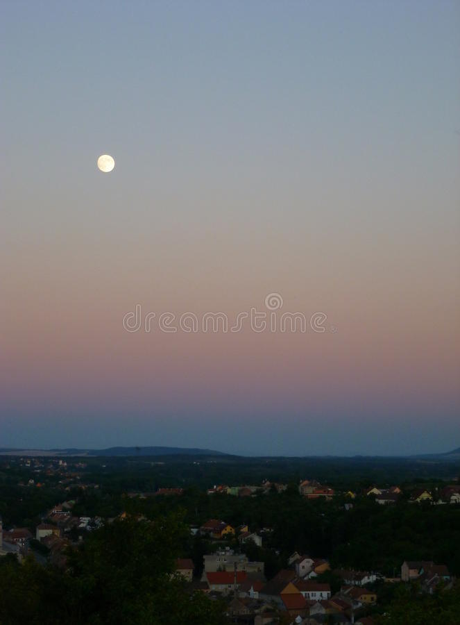 Full moon above a small town. Photo of a full moon above a small town stock photography