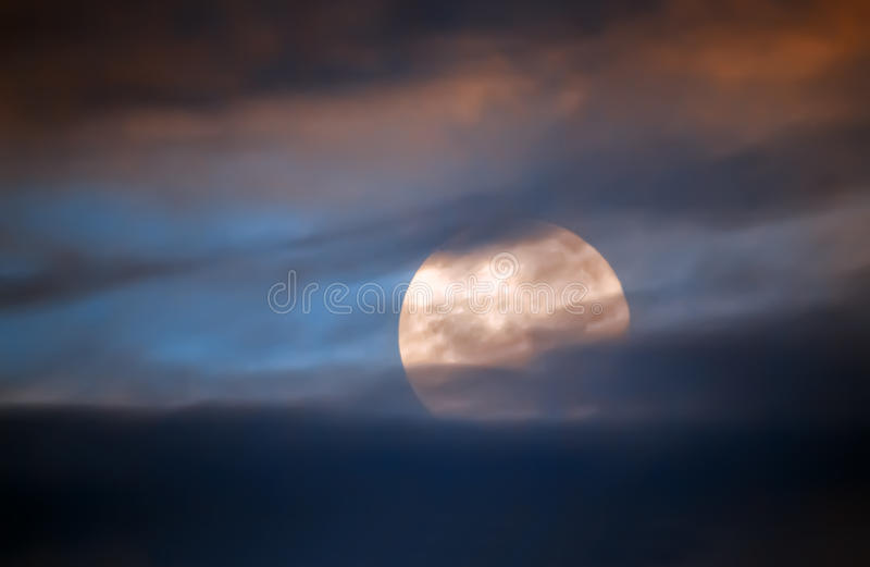 Full moon behind clouds stock images