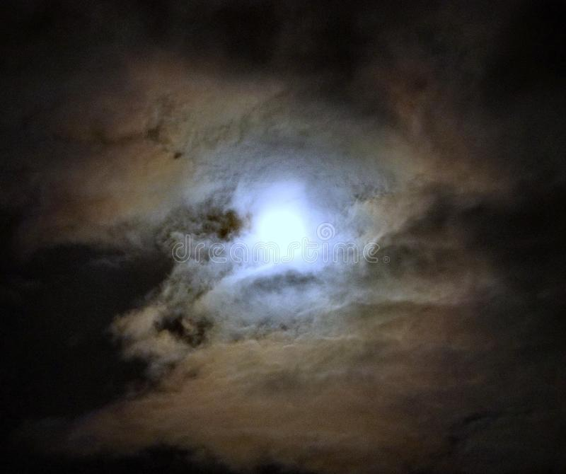 Moon after lunar eclipse and blue clouds royalty free stock image