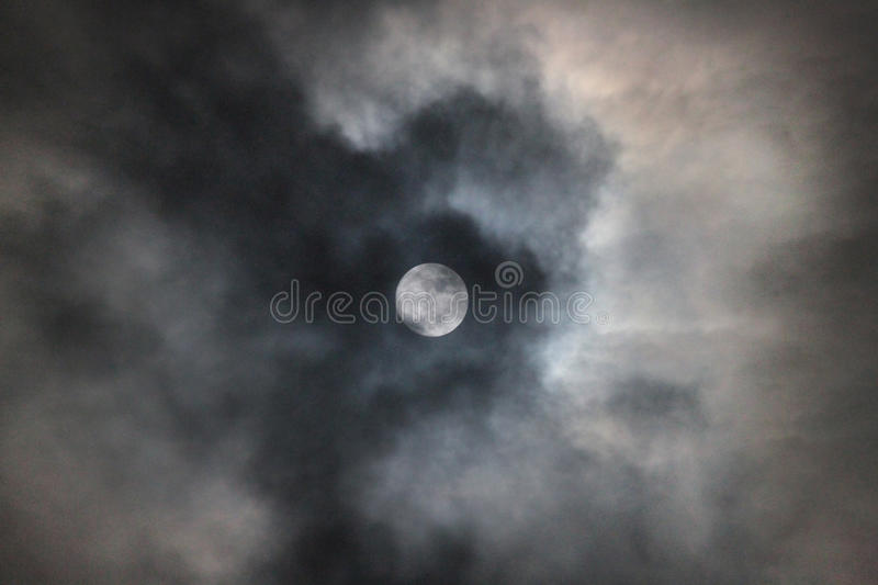 Full moon with clouds and lunar halo or ring. Twenty two degree halo or lunar ring around a full moon with clouds and colors of blue and orange. It is folklore royalty free stock photos