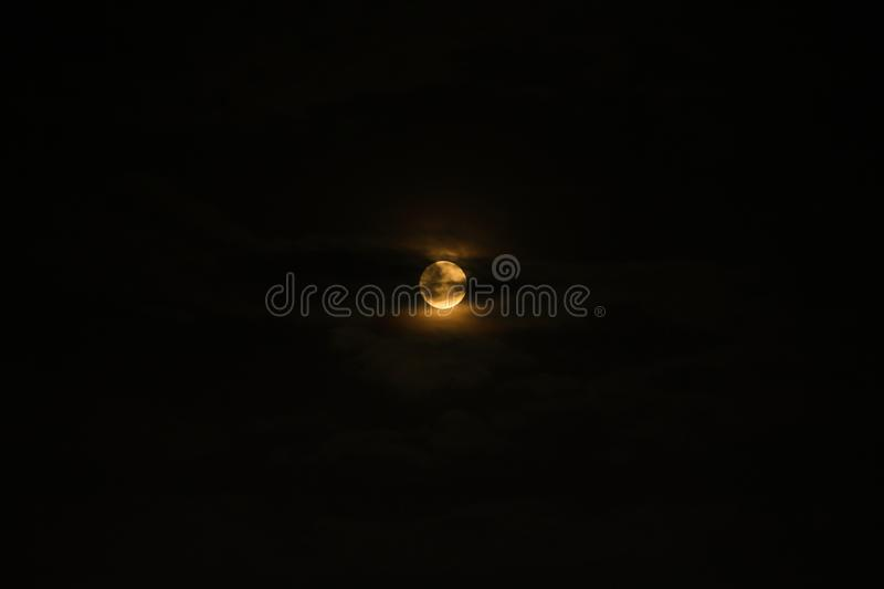 Full moon among the clouds in the dark sky stock photo