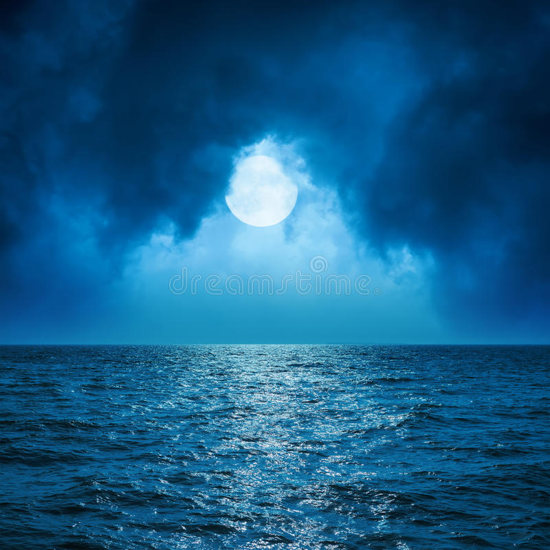 Full moon in clouds over dark sea royalty free stock images