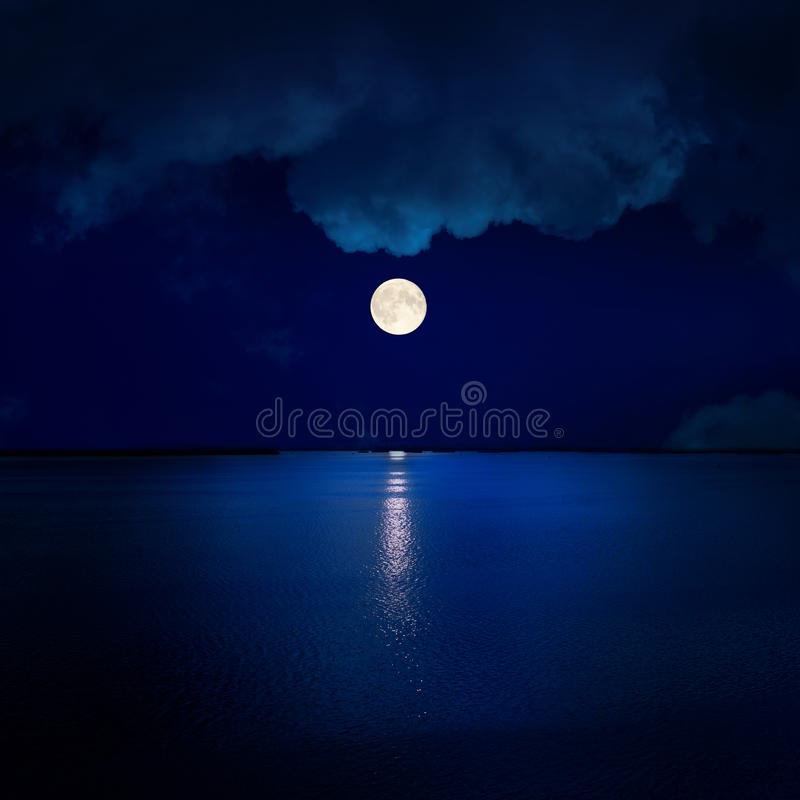 full moon in clouds over water stock photography