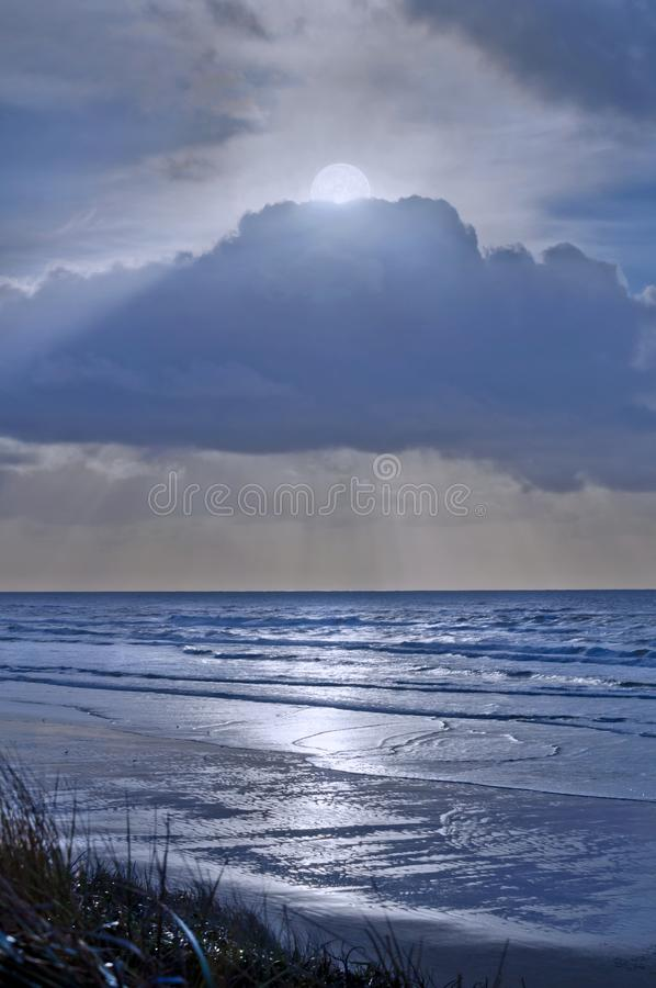 Full moon in clouds overlooking silver blue ocean water royalty free stock photos