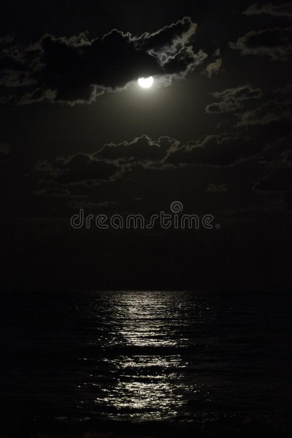 Full moon in a cloudy night sky reflecting moonlight on sea royalty free stock images
