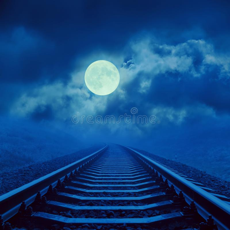 Full moon in clouds over night railroad royalty free stock photography