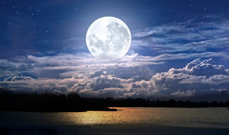 Full moon and cloudy sky. Over the night lake royalty free stock image