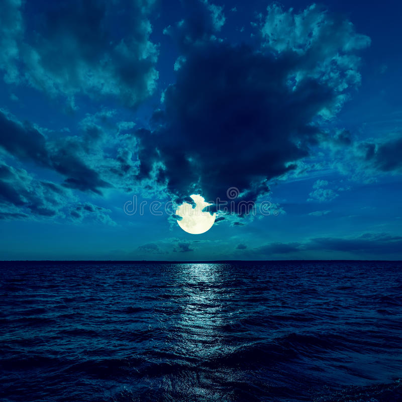 Full moon in dramatic sky over water stock photos