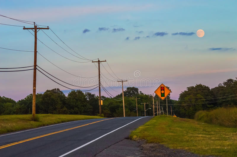 Full Moon and Highway. The full moon at dusk over a rural road in Freehold New Jersey stock images