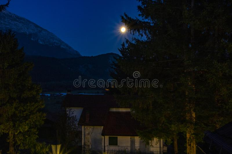 Full moon. A house and a huge pine tree under the moonlight at Pescasseroli, Italy stock images