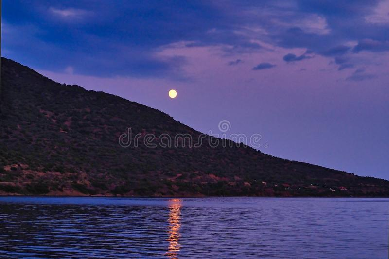 Full Moon Light Reflected in Sea Rising Over Treed Mountain Slope stock photos